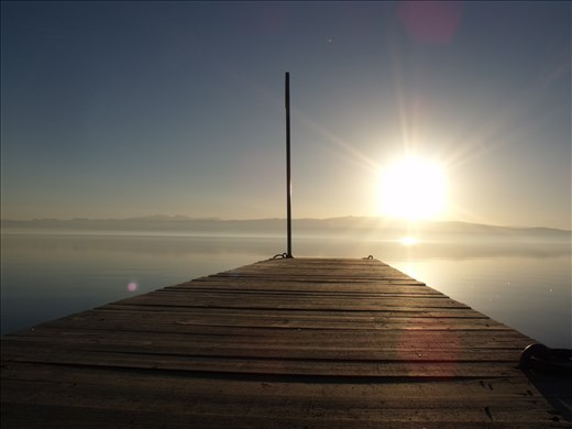The sun and the old wooden pier on Lake Ohrid. Friends through time.
