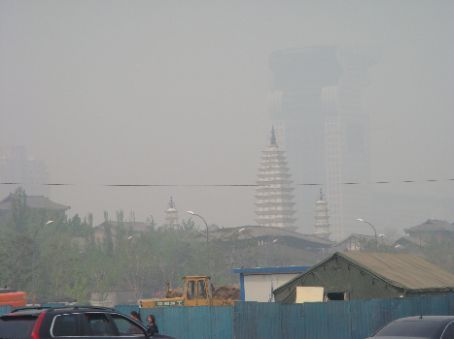 View of pagoda in front and large hotel building in haze in background