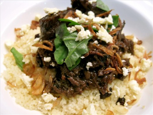 Lamb adobo, plated and served with feta, fried onions and basil over couscous.
