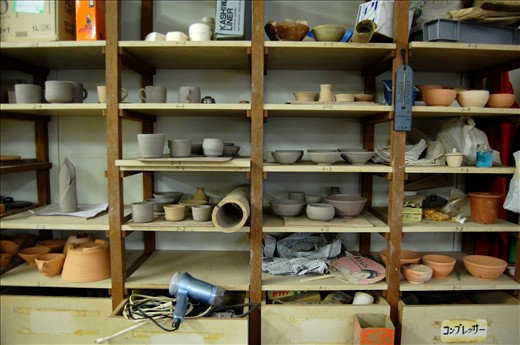The walls of the room are lined with cluttered pottery of varying stages of completion.