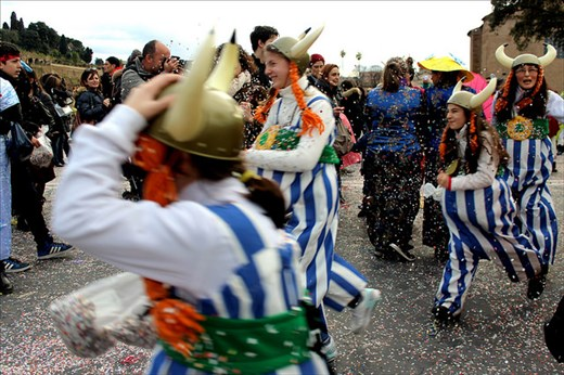 Romans celebrate Carnival in the street, with different, colorful costumes.