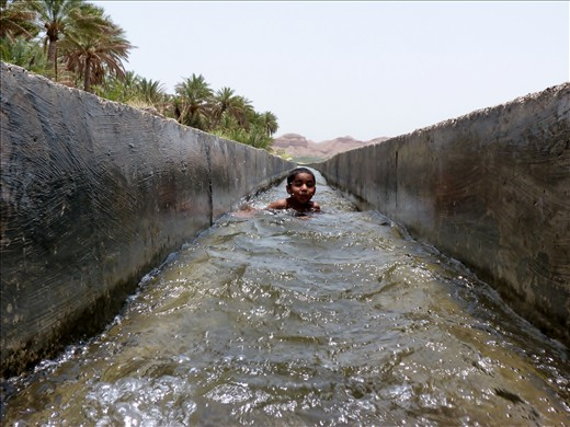 The oldest son of the family enjoys playing around in the aflaaj, the water system of Oman - The waters of life.
