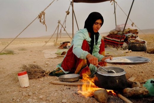 A Qash'qai girl cooks rice for dinner in front of her makeshift tent. Nomads make money by selling their herds, carpets, gabbeh or yoghurt drink in exhange for rice, clothes and other goods from the nearby towns or cities.