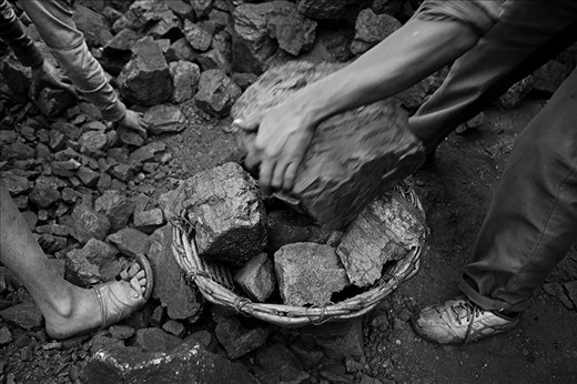 Pieces of coal and loading into wicker baskets for sell at black market.