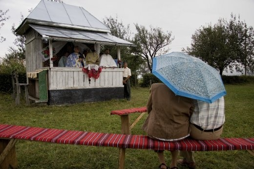 The last Christians get shelter under the umbrella while they wait for the end of the religious ceremony. Every year the local community celebrate the protecting saint of their former wooden church built around the 1700s.