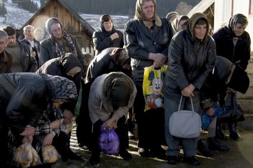 A group of peasants bow while praying during a funeral ritual on top of a hill. Modern elements like this bag portraying one of Disney's characters merge with local traditions in a critical moment for the Romanian cultural identity.
