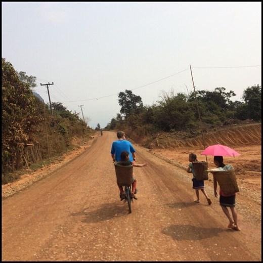 Kurt transportant sur son vélo sans vitesse une petite fille fatiguée de marcher.