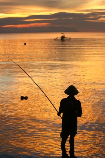 A local fisherman and traditional Balinese fishing boat Junkung make great silhouettes against a spectacular sunset at Lovina beach.