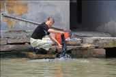 A woman cleans her clothes in outside of her back door in an unsanitary area of the Grand Canal: by firstimpressions, Views[384]