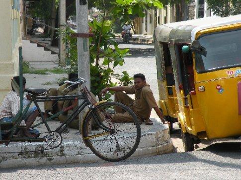 Choferes de rickshaw descansando en la vereda