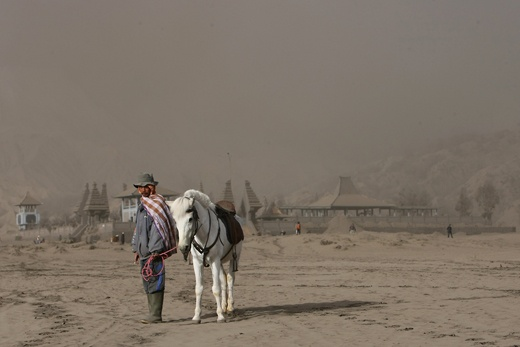 Tenger horseman in the volcano dust in Bromo caldera at Hindu themple waits for customers who hire the horse and him