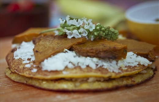 Cachapa in detail with a basil flower.
