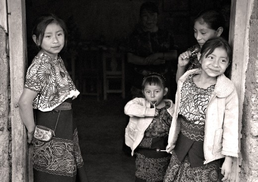 Village girls stand in the doorstep to their house.  Wonder upon their faces, beauty in their eyes; they speak a local native language that can only be learned when growing up in this mystical town.