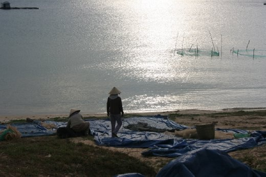 fisherwomen packing up at sunset after drying out the fish ready to prepare the fish sauce.