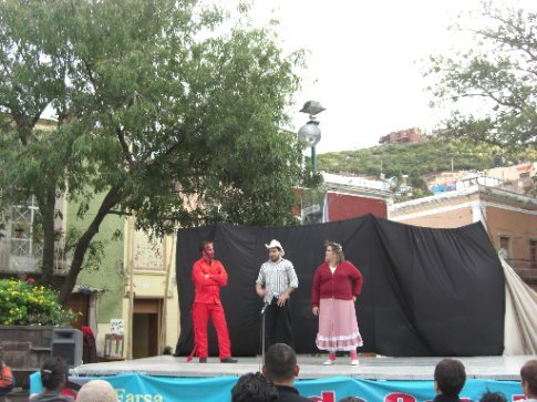 a weird theatre production in a square with angels and devils and stuff!