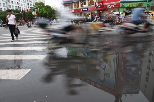 Traffic glides by in a blur at Sanya's busiest intersection on the island of Hainan, China. One woman braves the flow. The billboard atop KFC remains clear in the reflection only for a moment.