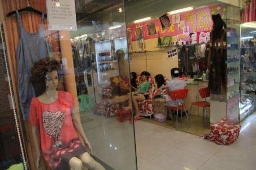 Pop music blares from three different directions amongst the labyrinth of 'Computer city' shops. A mannequin stares lifelessly through the glass. Three girls sit, with similar expressions, on a couch waiting for their toenails to dry. One plays on her phone.