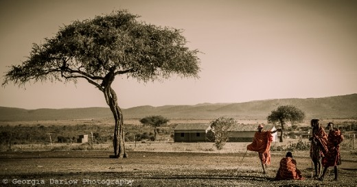 Some Maasai tribesmen catch up near a tree overlooking the Maasai Mara, Kenya