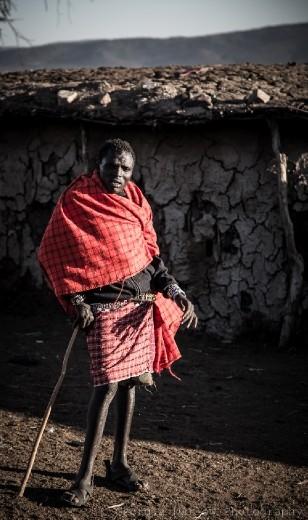 A Maasai tribesman stands near his hut in the Maasai Mara, Kenya