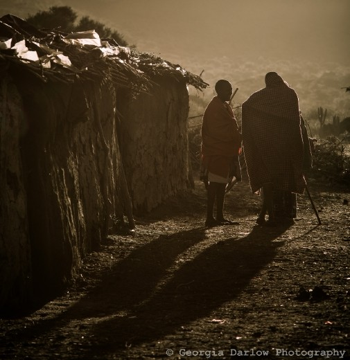A couple of Maasai tribesmen stand chatting at dusk.