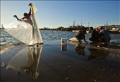 A young fisherman In Cienfuegos, Cuba watches an older man unfurl his net while he cuts bait. Fishermen come to the central pier just before dusk every night to catch the white fish that are then sold to local restaurants and fish mongers.: by grainfedphoto, Views[631]