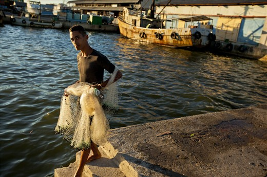 The young fisherman prepares to cast his net near the docks of the central pier.