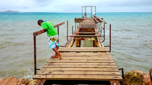 Broken Dreams - A Papuan boy stares down a broke pier in Port Moresby.