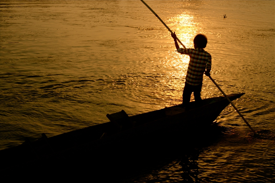 A boy in a dug-out canoe gliding down a river in Chitwan National Park.