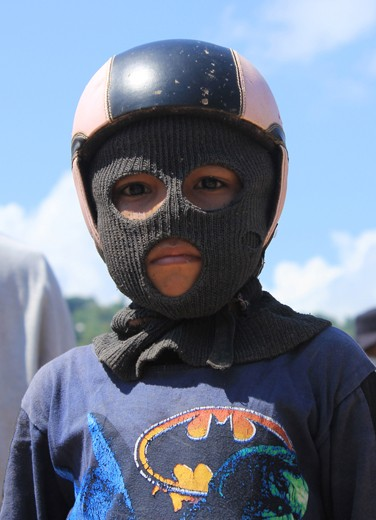 A kid with masker n helmet. It's needed to protect his face