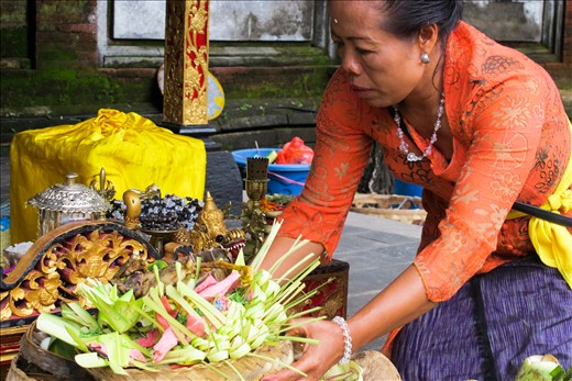 A woman dressed in traditional clothing is preparing 'Sampian' made from young white coconut leaf called 'Busung' which have sacred meaning for religious ceremony. 'Sampian' is carefully put and crafted to be presented to God.