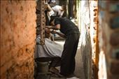 A man gets a shave in a tight lane of a slum: by hashimhakeem, Views[135]