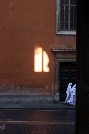Two nuns walking to church. Early morning Rome. With an almost holistic light.