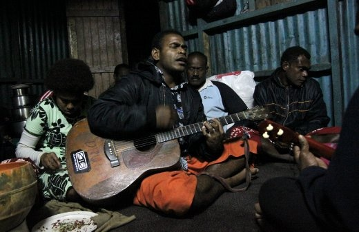 Local Fijian villagers sing and enjoy each other's company, while partaking in a