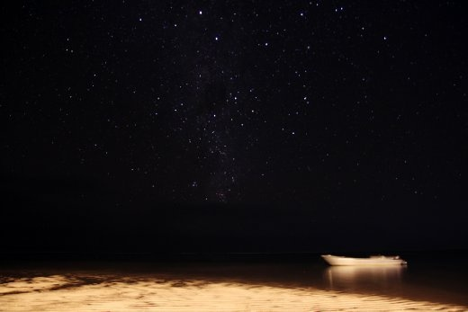 A local Fijian fisherman's boat sits quietly under the starry, South Pacific night sky.