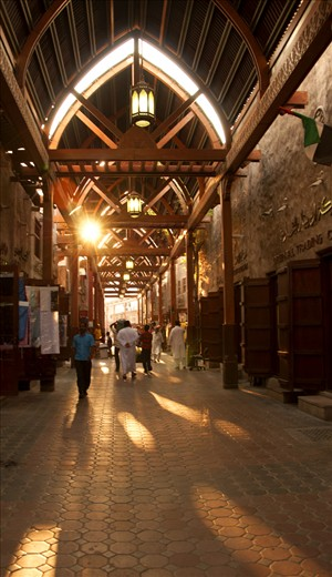Wooden archways hold the smell of spice & sunlight in Bur Dubai Souq
