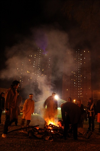 People build a fire in front of a housing estate