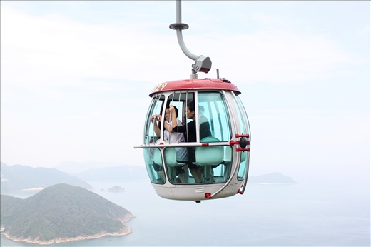 Visitors to Hong Kong's Ocean Park take photos of the view from the cable car