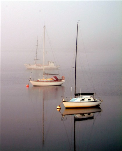 Early morning as the fog slowly lifts and three lonely boats dot the water.