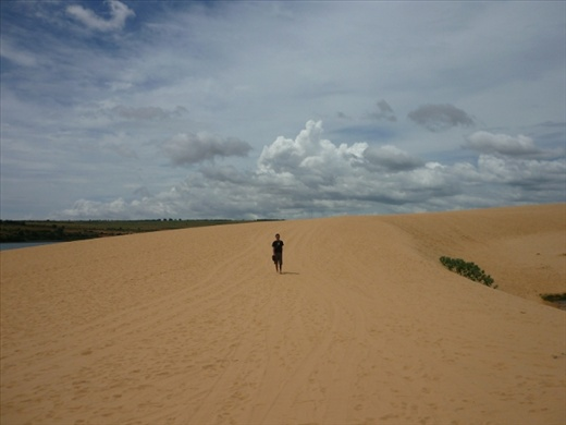 A dero dwarfed by the brown looking 'white sand dune'