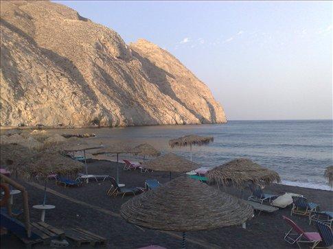 view of Perissa black sand beach on the island of Santorini, Greece.