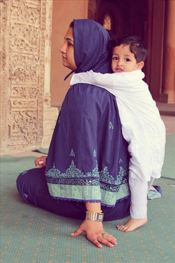 The kid is shy & holding his mum tightly.