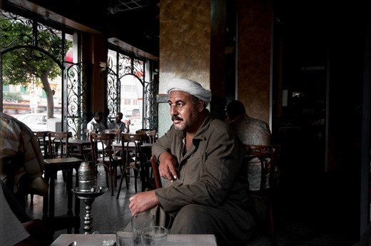 A portrait of a local man who dressed in the traditional Egyptian clothes. he was sitting in a coffe shop at the early morning to have breakfast and smoke some shisha, while other people chatting together at the background(left)