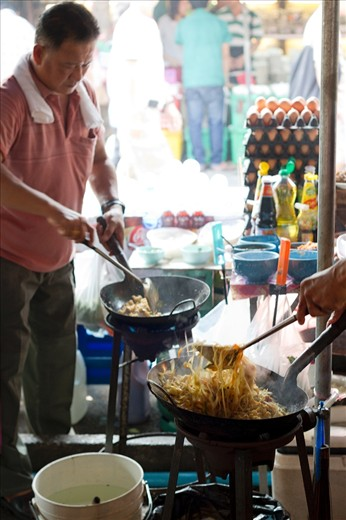 Chefs are cooking Pad Thai (possibly the most famous dish outside of Thailand) at the Chatuchak weekend market in Bangkok.