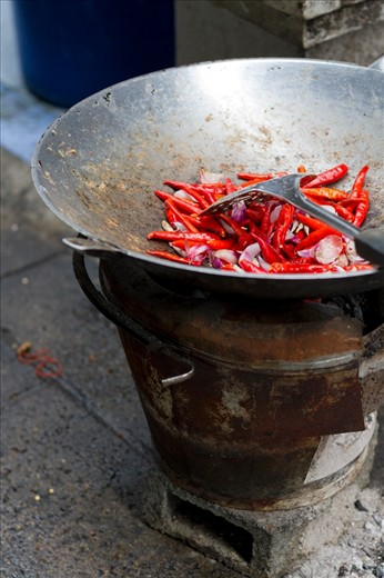 Essential Thai cuisine ingredients (chilli pepper, garlic and shallots) are ready to be cooked in a wok on an open fire stove under the Memorial Bridge in Bangkok, Thailand.