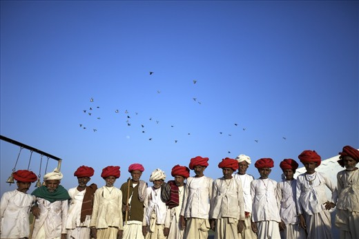Rabari men are waiting anxiously for the priest to open a tribal ceremony
