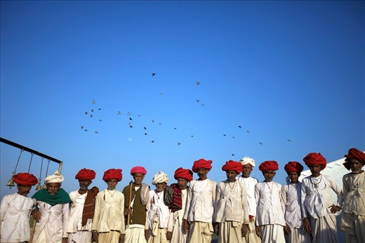 Rabari men are waiting anxiously for the arrival of a Priest to open a tribal ceremony