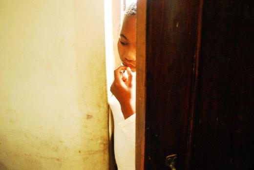 A young girl peers through the door