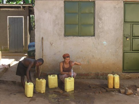 Mi and her new friend, Godfrey, fill jerry cans to filter for drinking water