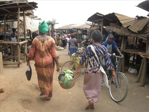 Mi and Teacher Sarah leave Kyotera market with groceries for dinner