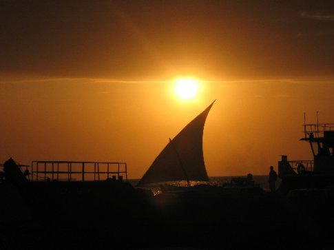 A dhow, the traditional ship of the Indian Ocean, sails by the western coast of Zanzibar at sunset.